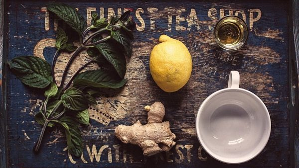 White cup with natural remedy ingredients ginger root and a lemon on a tray