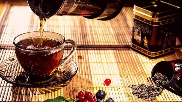 Tea being poured into a glass cup on a bamboo mat
