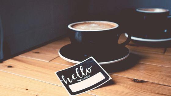 Black coffee mug with hello badge, achieve creative success together