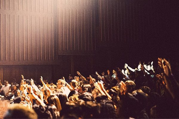 Crowded lecture room with hands raised