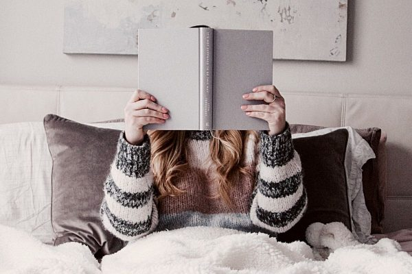A quiet person reading in bed, book covering her face.