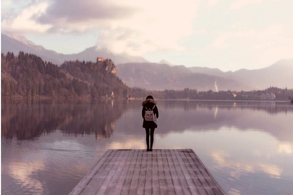 Quietly confident woman standing on a pier, facing a lake