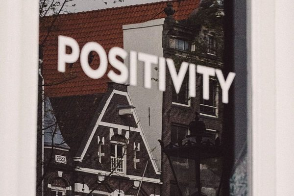Building reflected in window behind the word 'positivity' written in white