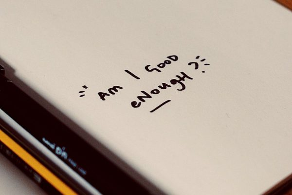 negative emotions written down as 'Am I good enough' on white paper beside pencils