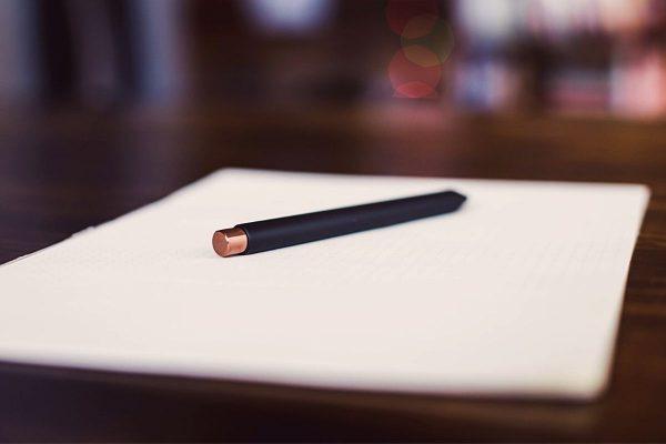 Black pen resting on top of white paper
