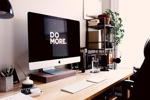 'Do More' motivational quote written on a black monitor on a desk