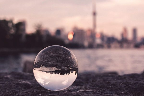 Glass orb on ground showing upside down perspective of city in background